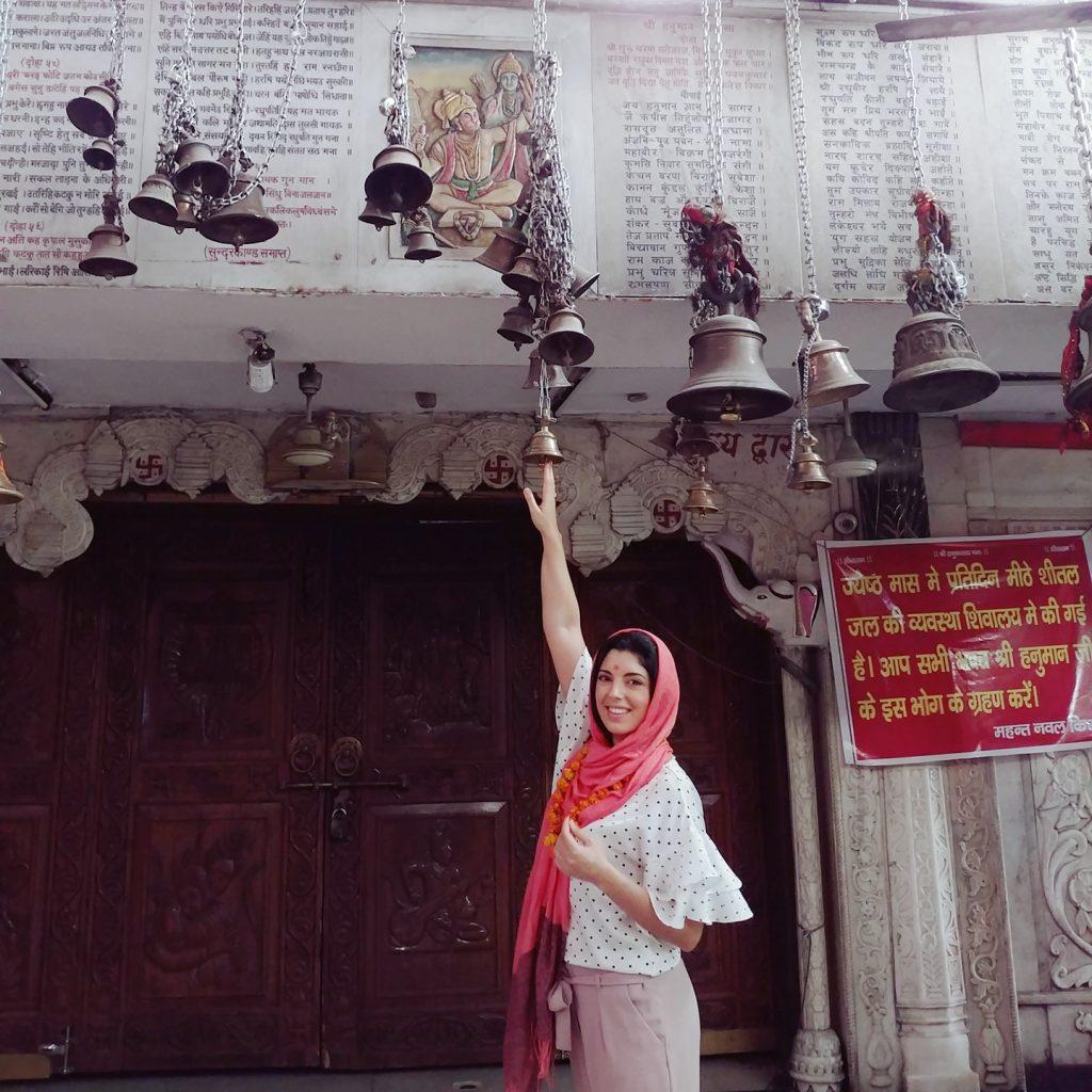 une touriste touche les cloches supendues au plafond du temple