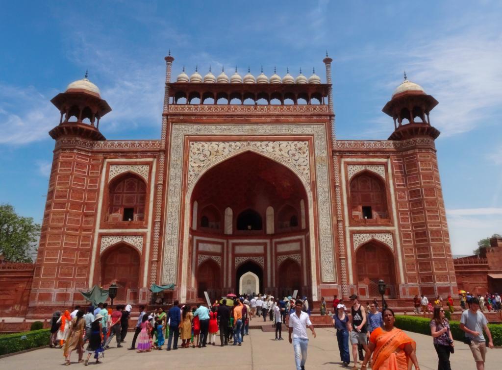 la grande porte d'entrée rouge où s'amasse la foule pour découvrir le Taj Mahal
