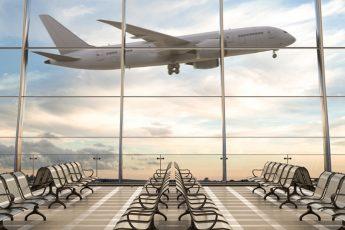 salle d'attente dans un aéroport avec un avion qui décole