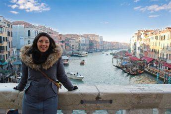une fille est assise sur la rambarde du Pont Rialto avec en arrière plan la vue du Grand Canal de Venise