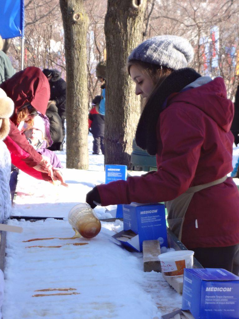 uen femme verse du sirop d'érable sur la glace pour faire des sucettes en sucre au Parc Jean Drapeau