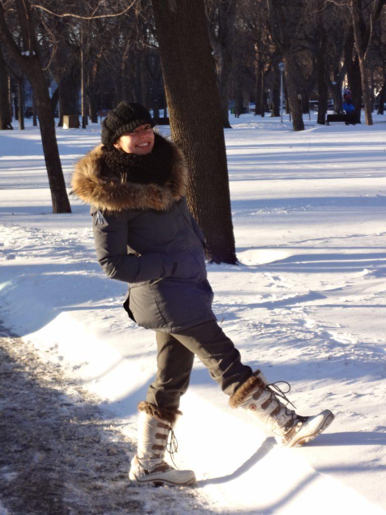 une fille montre la hauteur de neige dans un parc à Montréal