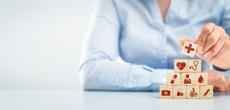 Une personne réarrange en une pyramide en bois avec des icônes médicales de soins de santé