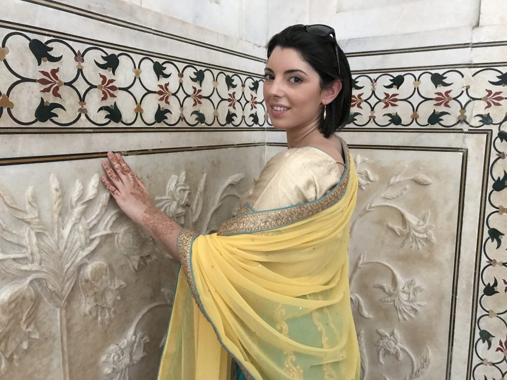 une femme admire les details architecturaux des murs du Taj Mahal